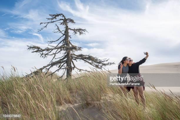 mixed ethnic sisters taking selfie on sand dunes, oregon coast - oregon coast stock pictures, royalty-free photos & images