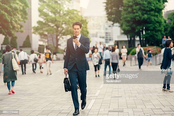Mixed ethnicity businessman texting on the phone