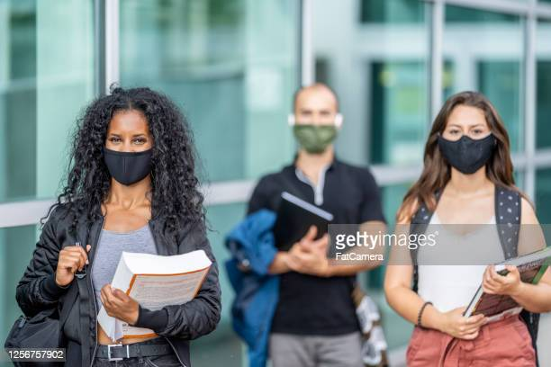 3 mixed ethnicity students wearing masks on campus - coronavirus stock pictures, royalty-free photos & images