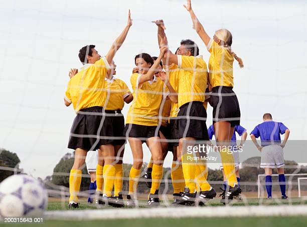 Mixed Football team celebrating goal at goal mouth, surface view