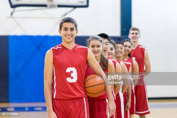 Mixed gender high school basketball team posing
