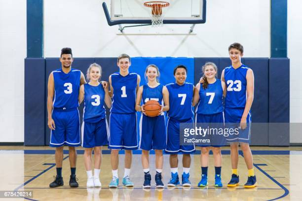 Mixed gender high school basketball team posing