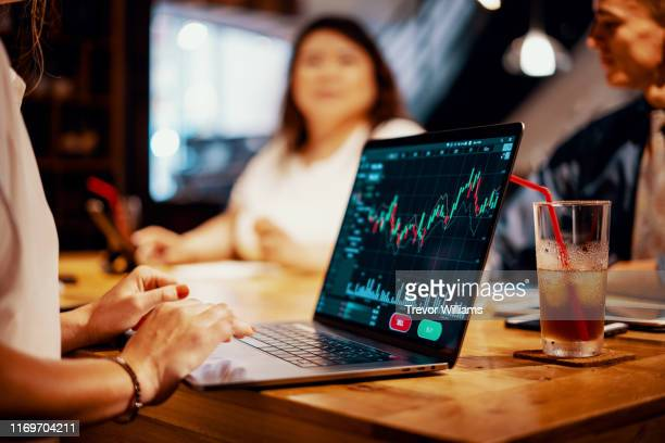mixed group of millennial aged friends discuss investing and cryptocurrency trading - financiën en economie stockfoto's en -beelden