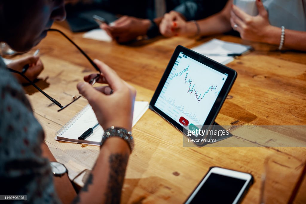 Mixed group of millennial aged friends discuss investing and cryptocurrency trading : Stock Photo