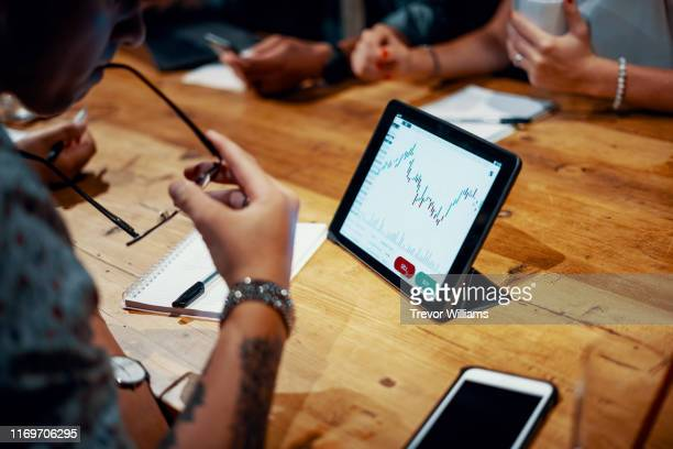 mixed group of millennial aged friends discuss investing and cryptocurrency trading - finance stock pictures, royalty-free photos & images
