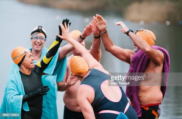 mixed group of open water swimmers celebrating after a swimming event - traje de mergulho - fotografias e filmes do acervo