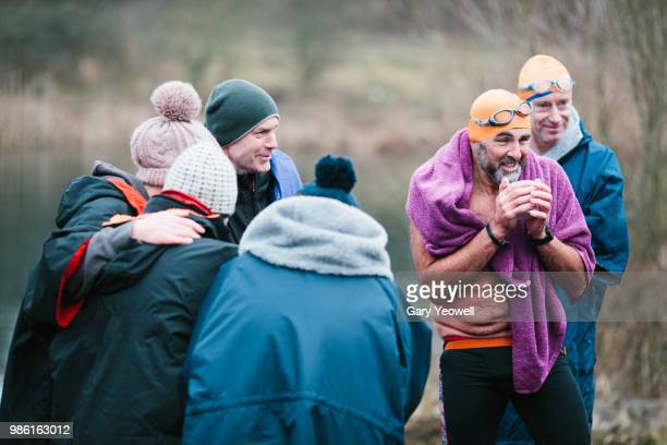 mixed group of open water swimmers relaxing after an event - swimming stock pictures, royalty-free photos & images