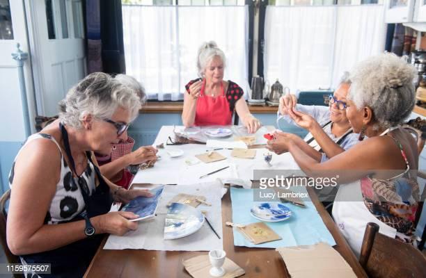 Mixed group of senior women at a new kintsugi workshop: fixing broken ceramics with golden glue