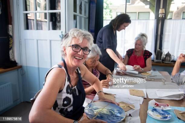 mixed group of senior women at a new kintsugi workshop: fixing broken ceramics with golden glue - environmental issues imagens e fotografias de stock