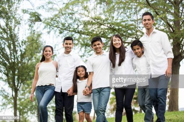 Mixed group of seven latin cousins smiling at camera