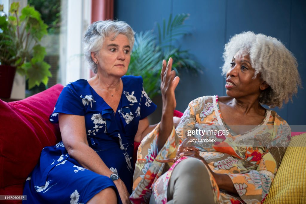 Mixed group of silver haired women meeting and sharing personal stories : Stock Photo