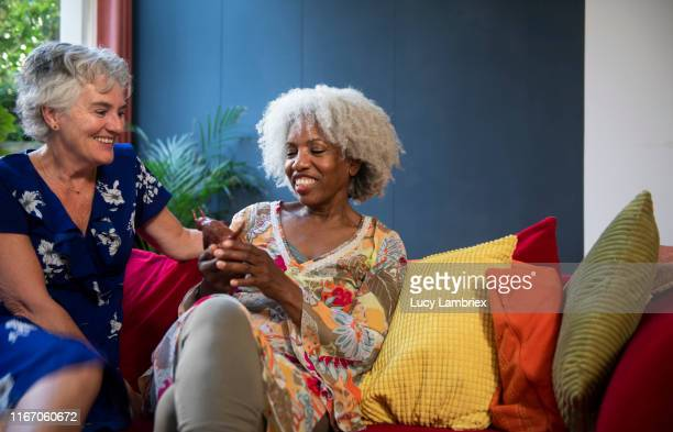 mixed group of silver haired women meeting and sharing personal stories - disruptagingcollection stock photos and pictures