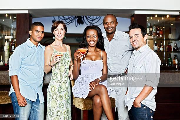 Gemischte Gruppe von lächelnde Junge Erwachsene trinken cocktails in der bar