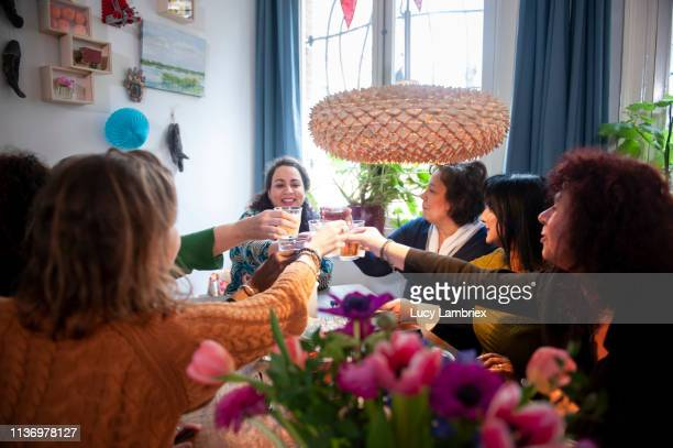 Mixed group of women celebrating friend's birthday with a party, bringing out a toast