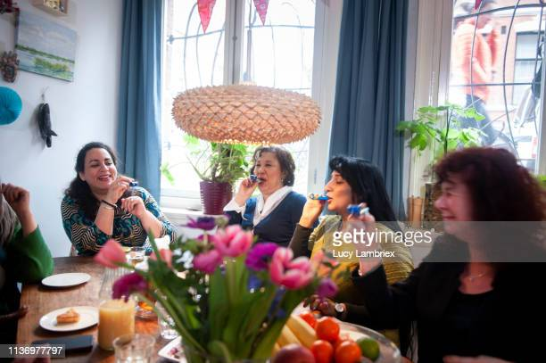 Mixed group of women celebrating friend's birthday with a party, playing with party horns