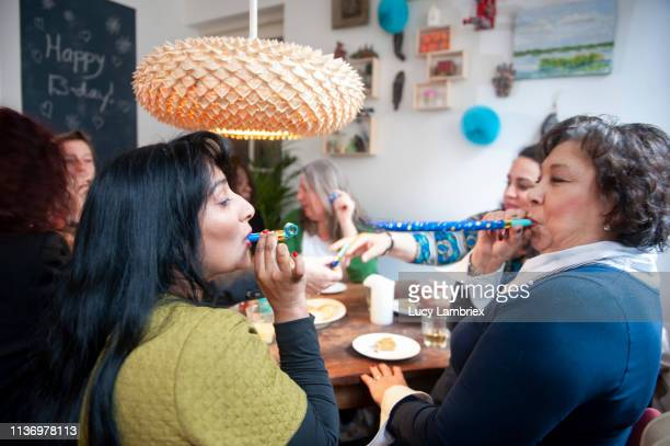 mixed group of women celebrating friend's birthday with a party, playing with party horns - lucy lambriex stockfoto's en -beelden