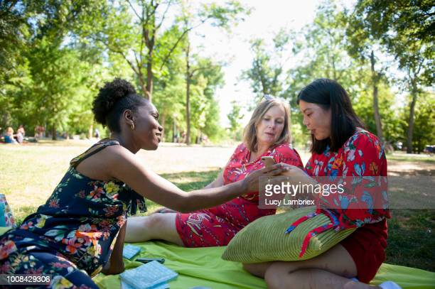 Mixed group of women looking at smartphone pictures in park