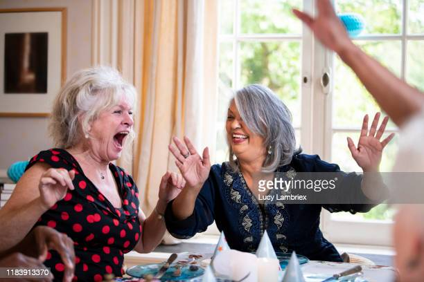 mixed group of women singing and cheering for their friend at her birthday party - lucy lambriex stockfoto's en -beelden