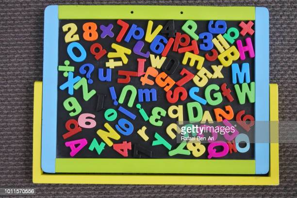mixed letters and numbers scattered on a magnet board - rafael ben ari stockfoto's en -beelden