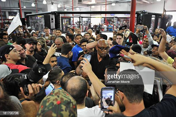Mixed martial artist Anderson Silva of Brazil autographs memorabilia for fans after a QA session at UFC Gym on September 23 2013 in Torrance...