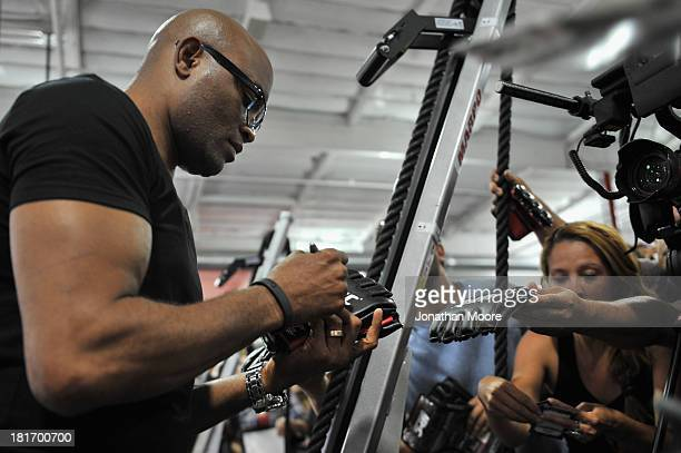 Mixed martial artist Anderson Silva of Brazil autographs UFC memorabilia for fans during a QA session at UFC Gym on September 23 2013 in Torrance...