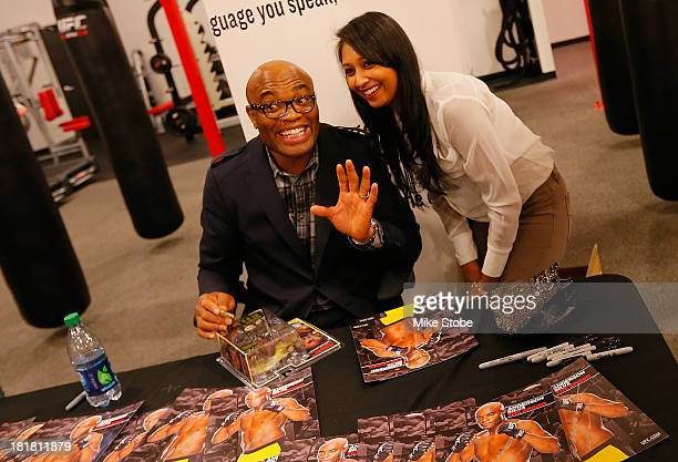 Mixed martial artist Anderson Silva of Brazil signs autographs for fans during a UFC autograph signing at UFC Gym on September 25 2013 in New York...