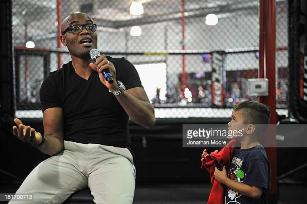 Mixed martial artist Anderson Silva of Brazil talks as a fan looks on during a QA session at UFC Gym on September 23 2013 in Torrance California