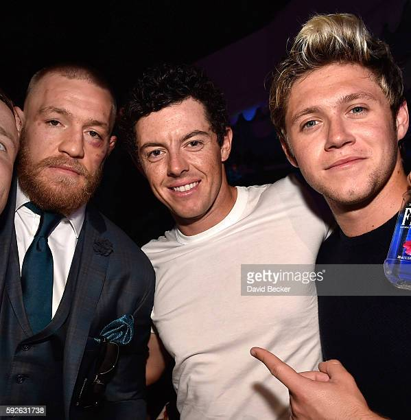Mixed martial artist Conor McGregor golfer Rory Mcllroy and singer Niall Horan celebrate McGregor's UFC 202 victory during the official afterfight...