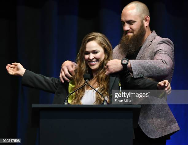 Mixed martial artist Travis Browne puts a UFC Hall of Fame jacket on his wife Ronda Rousey after she became the first female inducted into the UFC...