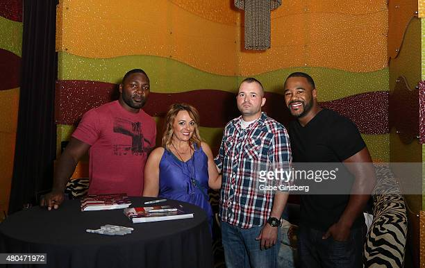 Mixed martial artists Anthony Johnson and Rashad Evans pose with fans during a UFC 189 viewing party as part of the International Fight Week events...