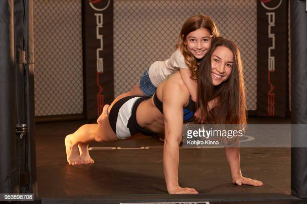 Portrait of bantamweight MMA fighter and former Olympic wrestler Sara McMann posing with her daughter Bella in octagon during photo shoot at Team...