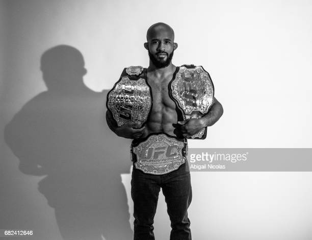 Portrait of UFC Flyweight champion Demetrious Johnson posing with belts during photo shoot at Time Inc Studios Johnson has succesfully defended his...