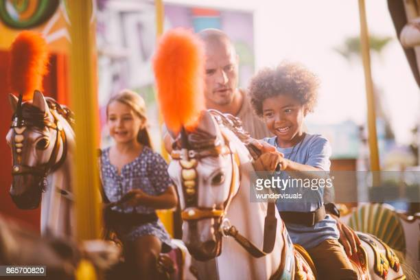 Mixed multi-ethnic family with father having fun on carousel ride