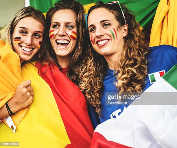 mixed national world supporter at the soccer stadium - soccer body painting stock photos and pictures