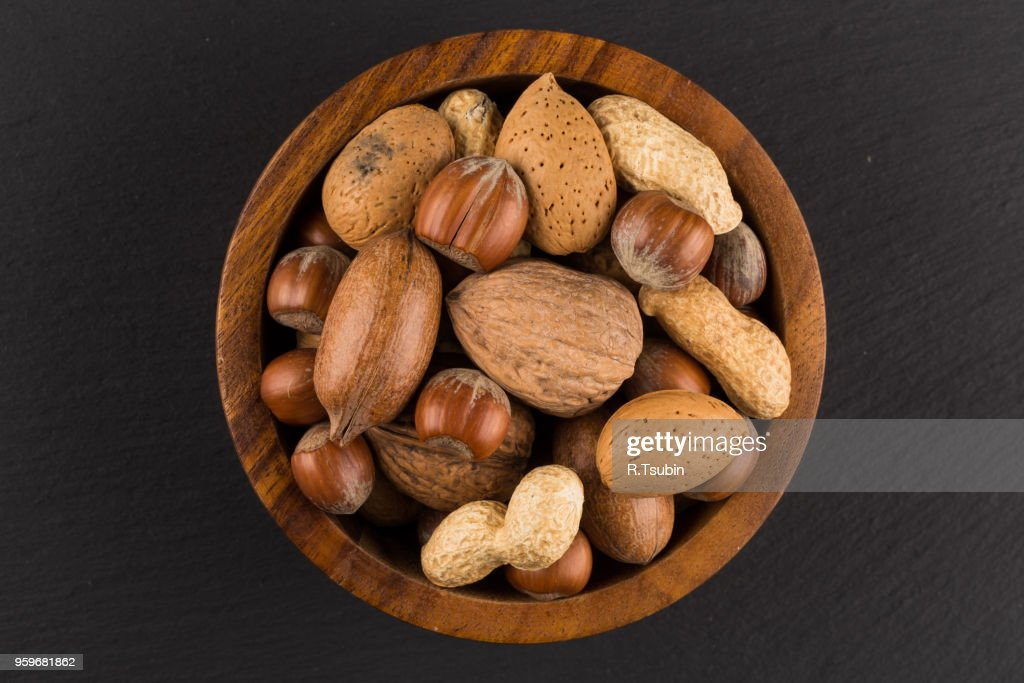 Mixed nuts in shells in a bowl a dark stone background : Stock-Foto
