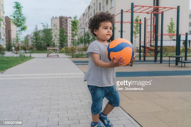 mestizo niño de 3 años jugando con pelota - 30 34 years fotografías e imágenes de stock