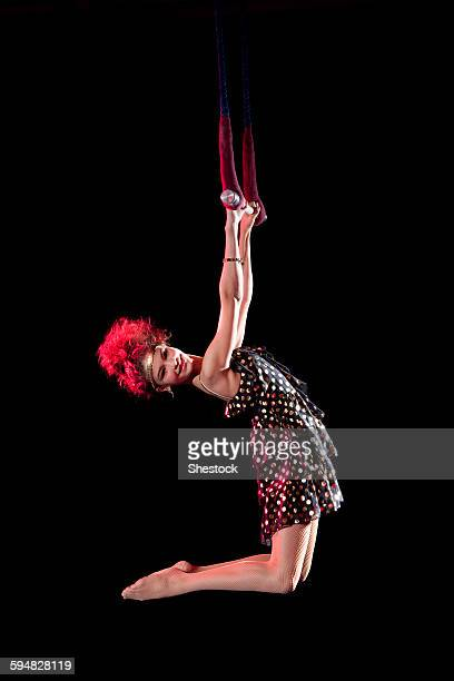 Mixed race acrobat hanging from trapeze