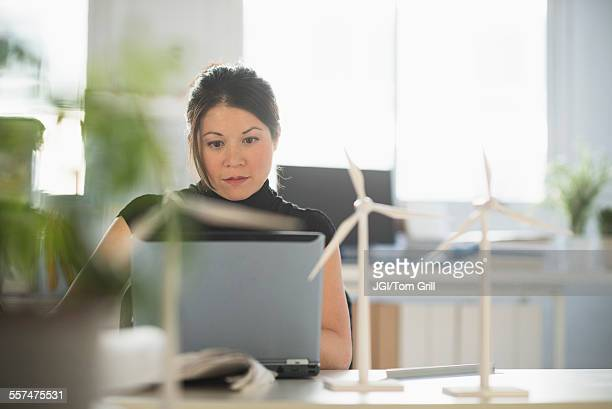 Mixed race architect with windmill models working on laptop