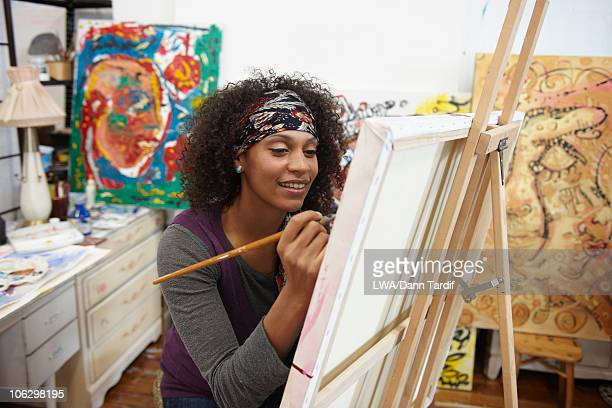 Mixed race artist painting in studio