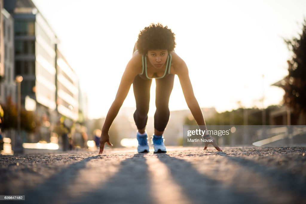 Mixed race athletic girl all set to run down the street : Stock-Foto