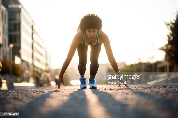 Mixed race athletic girl all set to run down the street