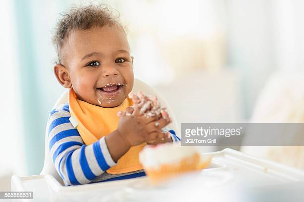 Mixed race baby boy eating in high chair