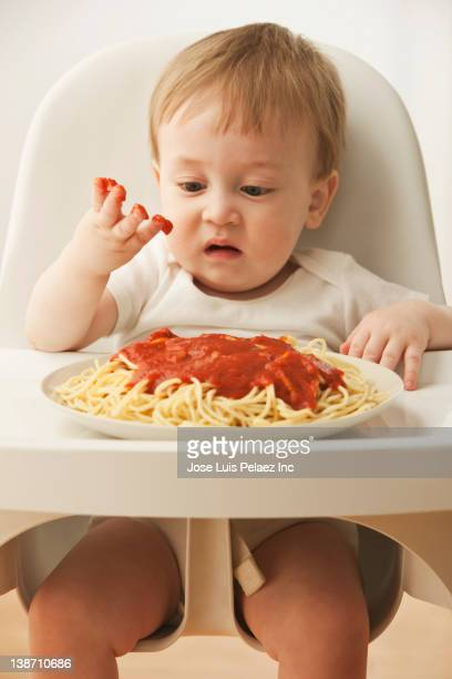 Mixed race baby boy eating spaghetti