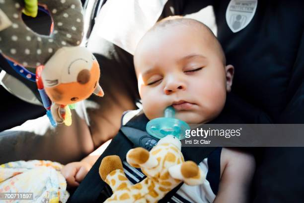 Mixed Race baby boy with pacifier sleeping in car seat