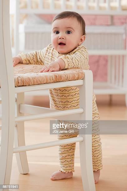Mixed race baby girl balancing near chair