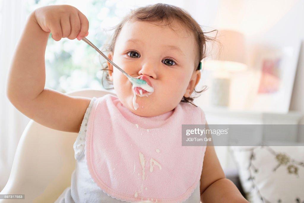 Mixed race baby girl eating yogurt : Stock Photo