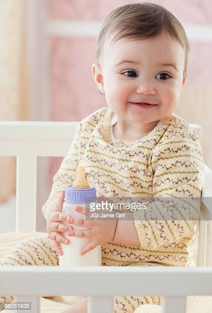 Mixed race baby girl holding bottle