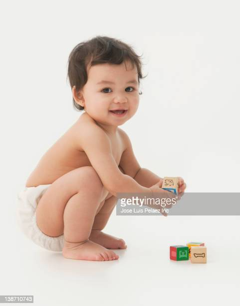 mixed race baby girl playing with alphabet blocks - diaper girl photos et images de collection