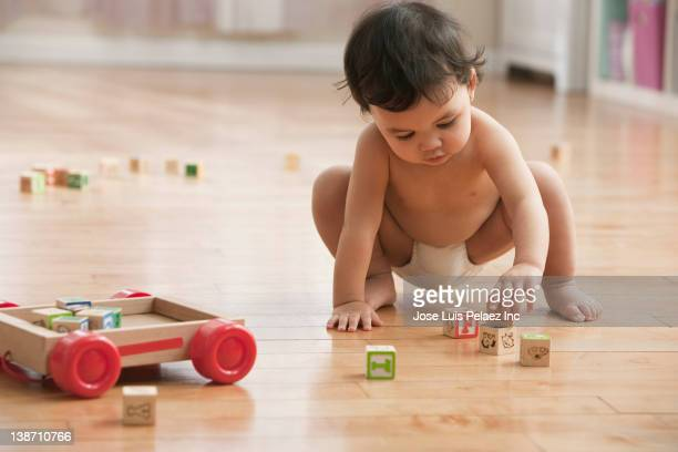 Mixed race baby girl playing with alphabet blocks