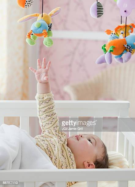 mixed race baby girl reaching for toy mobile - mobile stockfoto's en -beelden